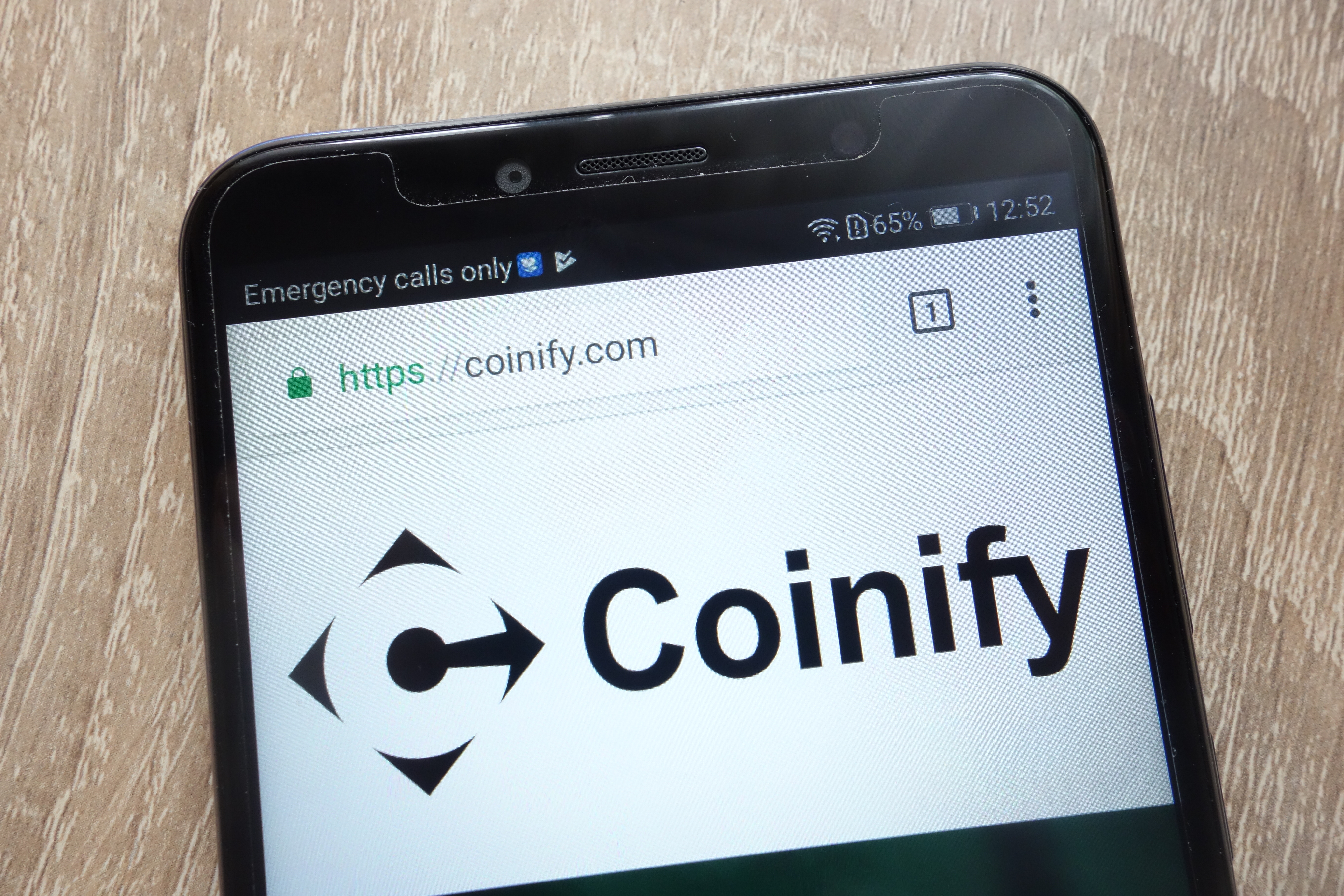Coinify logo on a phone.
